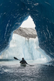 Sea Kayaker Paddles Through an Ice Cave Amongst Giant Icebergs Near Bear Glacier Photographic Print by  Design Pics Inc