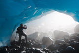 A Hiker Takes a Photograph of the Entrance of an Ice Cave from the Inside of the Mendenhall Glacier Photographic Print by  Design Pics Inc