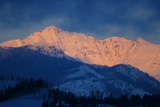 Morning Sun Lights Up a Snowy Mountain Range in Yellowstone National Park Photographic Print by Robbie George