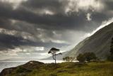 Sunlight Shingin Through the Storm Clouds over the Water Along the Coastline Papier Photo par  Design Pics Inc