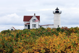 The American Flag Waves in Front of Maine's Nubble Lighthouse in Autumn Photographic Print by Robbie George
