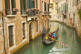 Tourists Ride in a Gondola in a Canal Winding Through Venice Photographic Print by Mike Theiss