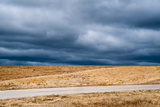 A Deserted Highway Cuts Through a Picturesque Landscape Beneath a Stormy Sky Photographic Print by Jim Reed