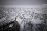 A Person Stands on the Bow of a Cruise Ship as it Plows Through Pack Ice Photographic Print by Jim Richardson