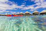 A Woman Kayaking in the Ocean at a Resort with Over-The-Water Bungalows Fotografisk tryk af Mike Theiss