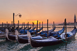 The Sun Rises Beyond Docked Gondolas at Saint Mark's Square in Venice Photographic Print by Mike Theiss
