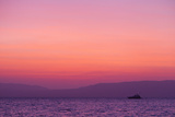 Sunset Turns the Sky Pink and Purple as a Lone Boat Floats Offshore Photographic Print by Mike Theiss