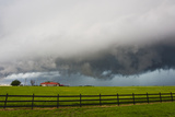 A Supercell Thunderstorm Darkens the Sky over a Ranch and Fields Photographic Print by Mike Theiss