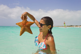 A Woman Holds Up a Starfish She Found in the Shallow Water Off of a Beach Photographic Print by Mike Theiss