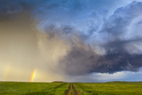 A Dirt Road Through a Field Seems to Lead to a Thunderstorm and Rainbow Photographic Print by Jim Reed