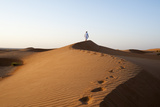 An Omani Man Walking Along a Sand Dune Ridge at Sunset Photographic Print by Sergio Pitamitz