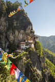 Prayer Flags Span the Chasm before the Tiger's Nest Monastery Photographic Print by Michael Melford