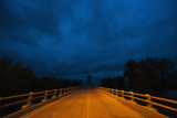 Stormy Sky over Bridge at Night Fotografisk tryk af Jim Reed