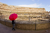 A Woman with a Red Umbrella Inside the Ancient Roman Colosseum Photographic Print by Mike Theiss
