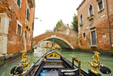 A View of Buildings and a Bridge from the Prow of Gondola in a Side Canal of Venice Photographic Print by Mike Theiss