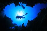 Scuba Divers Descend into an Underwater Cavern. Silhouettes against Sunburst Photographic Print by Rich Carey