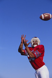 Football Player Catching a Football Photographic Print by  DLILLC