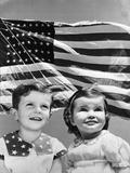 1940S PATRIOTIC COMPOSITE OF SMILING BOY AND GIRL OVER BACKGROUND OF THE AMERICAN FLAG BLOWING IN T Photographic Print by H Armstrong Roberts