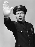 1950S MAN POLICEMAN IN UNIFORM HOLDING HAND UP IN AIR TOWARDS CAMERA STOP HALT WARNING LOOKING AT C Photographic Print by  DeBrocke