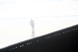 A Man Walks Near a Wall Separating Mexico and the United States in Tijuana Photographic Print by Eric Thayer