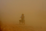 A Man Rides Through a Cloud of Dust Caused by Trucks Driving from a Construction Site Photographic Print by Sean Yong
