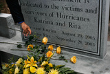 A Man Puts a Flower at the Monument Dedicated to the Victims and Survivors of Hurricane Katrina Photographic Print by Carlos Barria