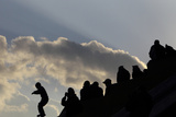 A Child Is Silhouetted as He Jumps from the Steps of a Temple in Kathmandu Photographic Print by Navesh Chitrakar