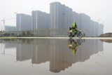 A Man Covers Himself with a Coat as He Cycles Past a Residential Complex under Construction Lámina fotográfica por Stringer China