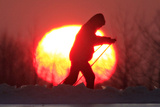 A Boy Skis, with the Sun Setting in the Background, in the Belarussian Town of Khoiniki Photographic Print by Vasily Fedosenko