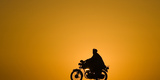 A Man Rides a Motorcycle as the Sun Sets at Delaram District in Nimroz Province Photographic Print by Marko Djurica