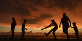 A Boy Hits a Ball as People Walk Along the Seafront at Galle Face Green in Colombo Photographic Print by Philip Brown