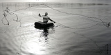 Fisherman Floating on a Rubber Tube Throws a Net to Catch Fish, Sabarmati River in Ahmedabad Photographic Print by Amit Dave