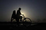 A Couple Is Silhouetted Against the Setting Sun as They Ride a Bicycle to their Residence Photographic Print by Mohsin Raza