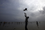 A Man Plays with His Child Against the Backdrop of Monsoon Clouds on a Beach in Mumbai Photographic Print by Danish Siddiqui