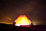 A Camper Is Seen Inside His Tent at Sunset in the Tatacoa Desert in Southwest Colombia Photographic Print by Jose Gomez