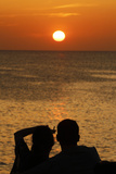 A Couple Watch the Sunset from the Balcony of a Bar Photographic Print by Enrique Calvo