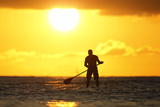 A Paddle Board Rider Surfs at Sunset on New Year's Eve at Waikiki Beach in Honolulu Photographic Print by Jason Reed