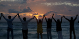 People Raise their Hands on a Beach During the Dawn of New Year's Day in Cancun Photographic Print by Victor Ruiz