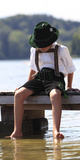 A Boy Wearing the Traditional Bavarian Leather Trouser 'Lederhose' Sits on a Boardwalk Photographic Print by Michaela Rehle