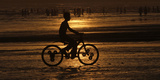 Boy Is Silhouetted Against Setting Sun While Riding a Bicycle at Karachi's Clifton Beach Photographic Print by Athar Hussain