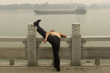 A Man Stretches His Leg on the Bank of the Han River as a Ship Passes by Amid Thick Haze in Wuhan Photographic Print by Darley Shen