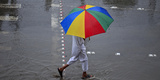 A Man Walks under an Umbrella on a Street During Heavy Monsoon Rain in Lahore Photographic Print by Mohsin Raza