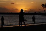 A Couple Embraces While Watching the Sunset on Waikiki Beach in Honolulu Photographic Print by Chris Wattie