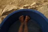 A Boy Takes a Bath in a Small Container Outside His Home at the Cerro Candela Shantytown in Lima Photographic Print by Pilar Olivares