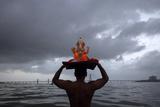 A Devotee Carries a Statue of the Hindu God Ganesh into the Arabian Sea Reproduction photographique par Vivek Prakash