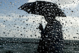 A Woman Walking with an Umbrella Is Seen Through Raindrops on a Car Window Photographic Print by Mike Hutchings