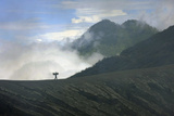 A Miner Carries a Load of Sulphur Out of Kawah Ijen Volcanic Crater in East Java Photographic Print by Laurence Tan