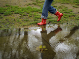 A Woman Wearing Rubber Boots Walks Near a Puddle in Boston, Massachusetts Photographic Print by Brian Snyder