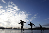 Three Men Skate on Frozen Flood Water in the Port Meadow Area of Oxford in Southern England Photographic Print by Eddie Keogh