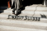 A Man Walks Past the Shadow of the Logo of Swiss Bank Credit Suisse in Zurich Photographic Print by Arnd Wiegmann